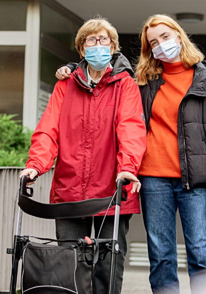 Mobile Mental Health - mom and daughter at retirement home looking happy and staying safe with masks